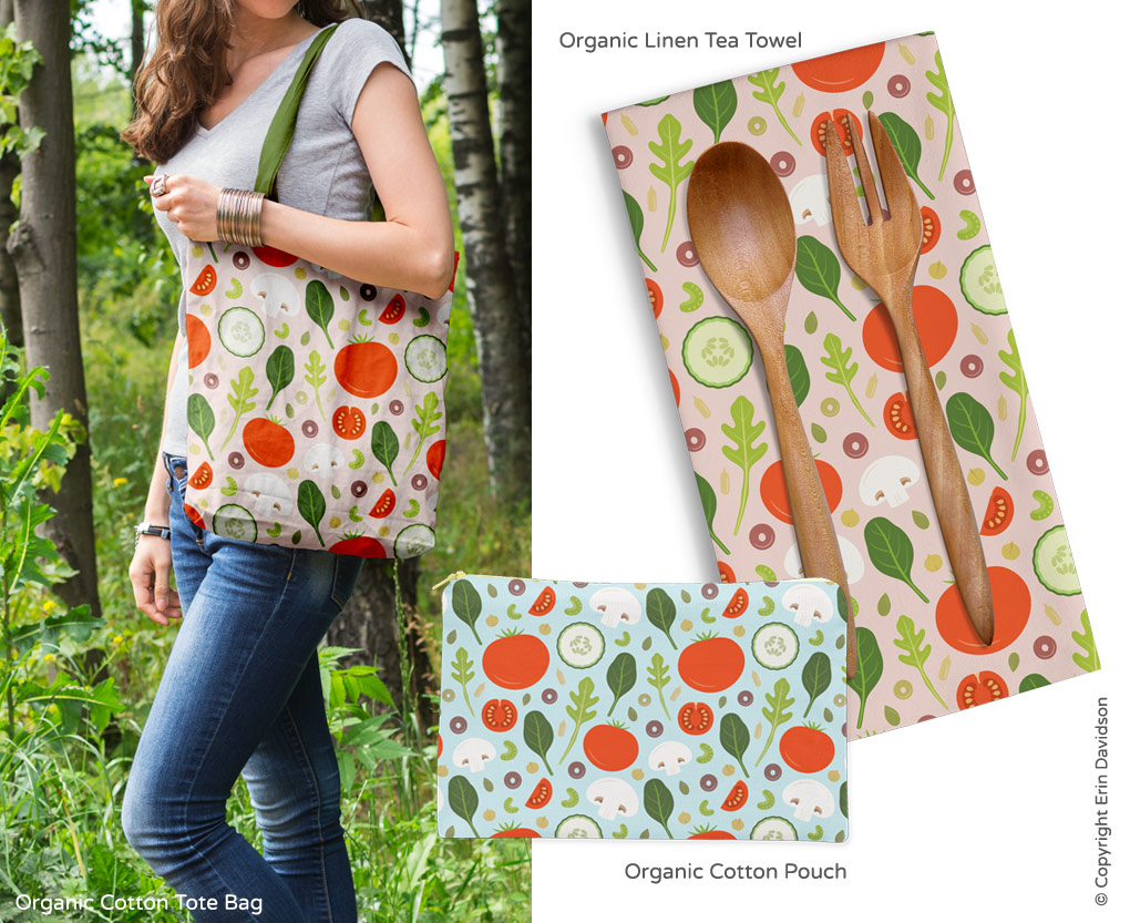 Person wearing an organic cotton tote bag printed with the Fresh Salad pattern, an organic cotton pouch featuring the pattern with blue colorway, and organic linen tea towels featuring the pattern in pink colorway. Wooden spoon and fork are sitting on the tea towel.